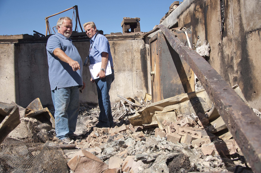 Michael Mangum | The Salt Lake Tribune | Val Johnson, left, examines the rubble of his home for belongings with friend and insurance adjuster Glenn Johnson on Saturday, September 25, 2010. Johnson lost his him to the Machine Gun fire earlier in the week.
