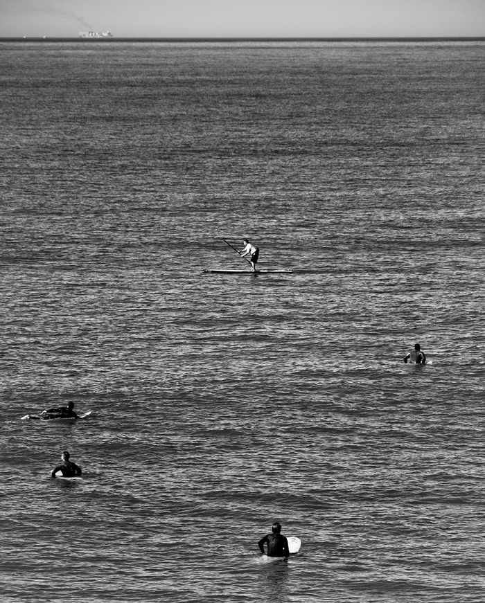 Surfers wait to catch a wave just off the coast of Huntington Beach near southern California on Friday, February 17, 2012. | Photo by Michael Mangum