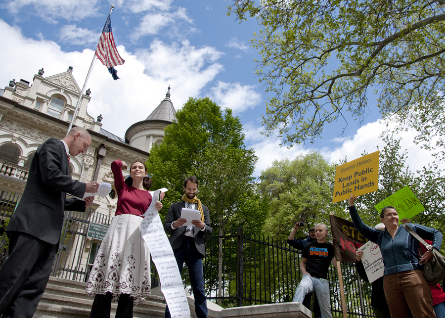 """TIM TRACY, far left, in mock representation of executives in the energy industry, MELANIE MARTIN, as a protestor and holding a """"List of Complaints,"""" and JESSE FRUHWIRTH, representing Governor Gary Herbert, perform a skit at a protest in front of the Governor's Mansion in Salt Lake City, Utah, on Friday, April 27, 2012, illustrating a business relationship they say exists between energy companies and the Utah Legislature. Protestors voiced concern over Governor Herbert's challenge of federal control over public lands in Utah and ultimately hope to prevent strip mining and oil drilling in the state of Utah. 