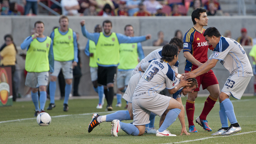 Real Salt Lake defender TONY BELTRAN (2) walks out of the area while Minnesota Stars FC players jubilate and surround SIMONE BRACALELLO (10) after Bracalello scored Minnesota's third goal in third-round action of the Lamar Hunt U.S. Open Cup at Rio Tinto Stadium in Sandy, UT on Tuesday, May 29, 2012. Minnesota defeated Salt Lake 3-1 and will advance to the fourth round. | Photo by Michael Mangum