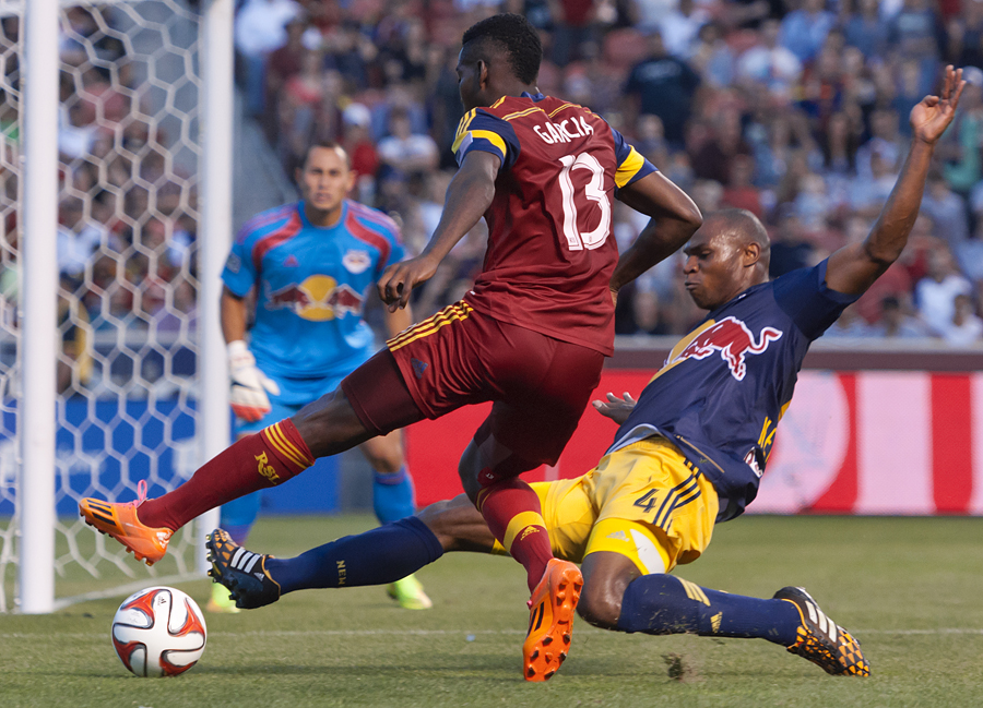 New York Red Bulls defender Jamison Olave (4) slide tackles an onrushing Real Salt Lake forward Olmes Garcia (13) during the second half of their match at Rio Tinto Stadium in Sandy, UT on Wednesday, July 30, 2014. The match ended in a 1-1 draw.  Michael Mangum  |  ChangingMyLens.com